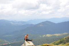 Male gymnast doing gymnastic exercise in the mountains Stock Photos