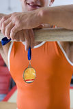 Male gymnast with gold medal, arms on bar, mid section Royalty Free Stock Image