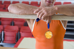 Male gymnast with gold medal, arms on bar, mid section Royalty Free Stock Photo