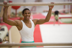 Male gymnast with hands on parallel bars, smiling, portrait Stock Photography
