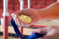 Male gymnast holding gold medal, close-up of hands Stock Photos