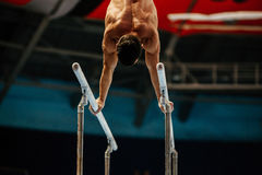 Male gymnast naked torso. Exercises on parallel bars Stock Photography