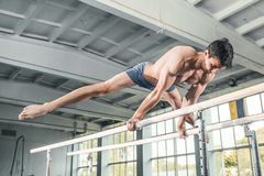 Male gymnast performing handstand on parallel bars. At gym Royalty Free Stock Photo