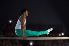 Male gymnast performing on parallel bars, side view stock images