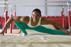 Male gymnast stretching in gymnasium, smiling, portrait royalty free stock photos