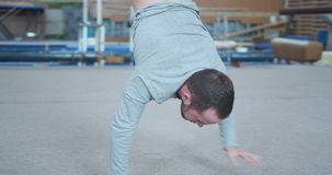 Male gymnast walking on hands at gym stock video footage