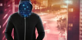 Composite image of male hacker in black hoodie standing. Male hacker in black hoodie standing against high angle view of crowded buildings in city Royalty Free Stock Images