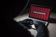 Male hacker hacking into computer operating system. Internet security malware virus Trojan ransomware system breached concept Royalty Free Stock Photography
