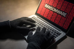 Male hacker hand hacking into computer operating system. Internet security malware virus Trojan ransomware system breached concept Royalty Free Stock Images