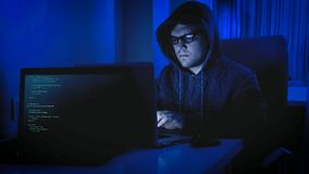 Portrait of male hacker in hoodie sitting in dark room and working on computer. Male hacker in hoodie sitting in dark room and working on computer Royalty Free Stock Images