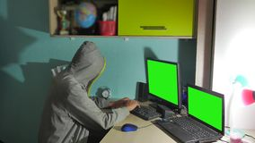 Male hacker indoor working on a computer. man hacker in hood hiding his face stock video footage