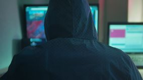 Male hacker internet working on a computer. man hacker indoor in hood hiding his Internet face stock video footage