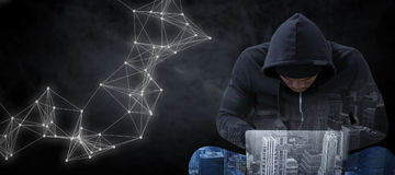Composite image of male hacker using laptop while sitting Stock Photography