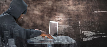 Composite image of male hacker using laptop on table Stock Photo