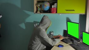 Male hacker working on a computer. man hacker in hood hiding his face indoor stock video