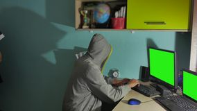 Male hacker working on a computer. man hacker in hood hiding indoor his face stock video footage