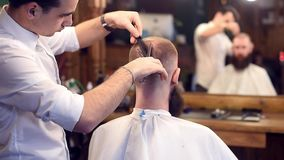 Man barber cutting hair with scissors in male hair salon. Cropped male client sitting back. Blurred reflection in mirror. Male haircutter in action during men`s stock video footage