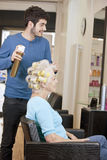 A male hairdresser applying hairspray to a female clients hair Stock Images