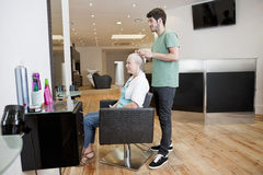 A male hairdresser applying product to his female clients hair Royalty Free Stock Images