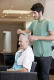 A male hairdresser combing a female clients hair Stock Images