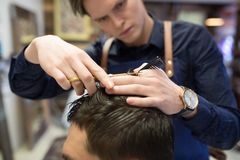 Male hairdresser cutting hair at barbershop royalty free stock photography
