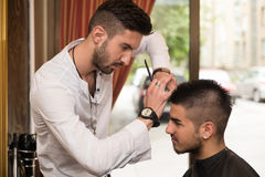Male Hairdresser Cutting Hair Of Smiling Man Client Stock Photography