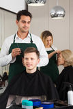 Male hairdresser cutting hair of teenage guy. In hair salon royalty free stock photography