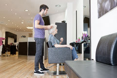 A male hairdresser discussing a female clients hair Stock Photos