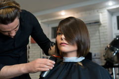 Male hairdresser does a haircut to pretty woman Stock Image