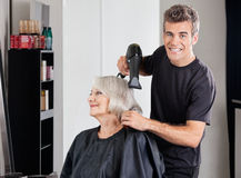 Male Hairdresser With Dryer Setting Customer's Royalty Free Stock Image