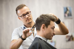 Male hairdresser making haircut. Working process in modern barbershop. Male hairdresser serving client, making haircut using metal scissors. Side view of stock photos