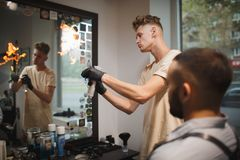 A stylish barber preparing tools for traditional beard shave on a barbershop background. Fire haircut concept. royalty free stock images