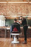 Male hairdresser trimming hair of customer Stock Photos