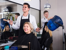 Male hairdresser at the work. Smiling male hairdresser doing hairstyle for elderly blonde women in hairdressing saloon Stock Image