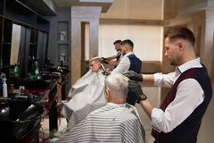 Male hairdressers grooming client`s haircuts in barbershop. Side view of professional male hairdressers working in modern barbershop with clients. Masters in stock photography