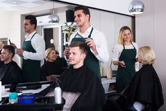 Male hairstyler serving teenager. In salon Stock Photos