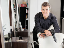 Male Hairstylist With Hairdryer Leaning On Chair Stock Image