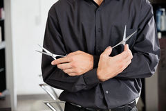 Male Hairstylist Holding Two Scissors. Midsection of male hairstylist holding two scissors at salon Royalty Free Stock Images