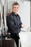 Male Hairstylist With Scissors Leaning On Cabinet Royalty Free Stock Photo
