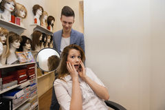 Male hairstylist showing hair to worried female customer in salon Royalty Free Stock Photos