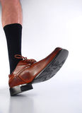 Male hairy leg with black sock and brown shoe. Stock Image