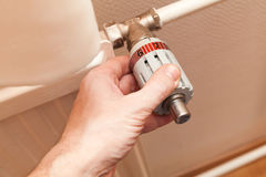 Male hand adjusts heat control on a radiator Royalty Free Stock Photo