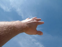 Male hand against blue sky Royalty Free Stock Photo
