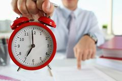 Male hand on the alarm clock a red. Color stands in the office on the table showing seven o`clock in the morning or evening AM PM royalty free stock photography
