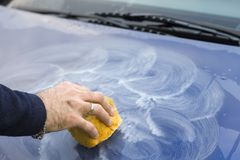 Male hand applies polishing paste on car paint with sponge. Male hand applies white polishing paste on blue car paint with yellow sponge Royalty Free Stock Photo