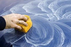Male hand applies polishing paste on car paint with sponge. Male hand applies white polishing paste on blue car paint with yellow sponge Stock Photo