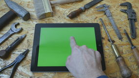 Male hand of artisan craftsman using tablet pc with green screen in workshop. Top view. Different vintage tools lie. Beside stock video