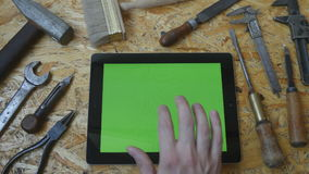 Male hand of artisan craftsman using tablet pc with green screen in workshop. Top view. Different vintage tools lie. Beside stock video footage