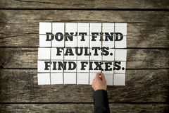 Male hand assembling a Don't find faults. Find fixes sign Stock Image