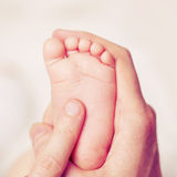 Male hand with baby feet Stock Photo